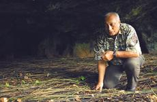 Chris Reyes, a World War II survivor, crouches in one of the caves where islanders, including his family, hid during the Japanese occupation of Guam.