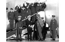 Cmdr. Lloyd Bucher, front left, and USS Pueblo crew members wave to the crowd as they prepare to leave Kimpo Air Base.