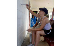 Petty Officer 3rd Class Deanna Mentzel paints the community center in Agat, Guam, during a cleanup project Saturday.