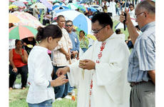 Marissa Laracuente, 11, receives Holy Communion from Father Carl Vila during the All Souls Day Mass on Wednesday in the Guam Veterans Cemetery.