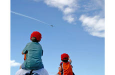 Hayden Froehlich, 5, left, was among the children using the shoulders of adult friends and parents to get a bird's-eye view of the Thunderbirds practice show on Saturday