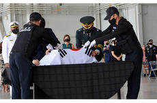 South Korean officials cloak their national flag over a box holding the remains of a countrymen who died during the Korean War during a repatriation ceremony at Joint Base Pearl Harbor-Hickam, Hawaii, Tuesday, June 23, 2020.