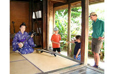 Tomiko Shimabukuro plays the sanshin for a family from Tokyo visiting Ryukyu Mura, a folk village sometimes referred to as Okinawa's Williamsburg.