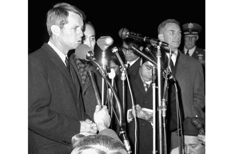 Robert Kennedy speaks to reporters and well-wishers at Yokota. At right is the U.S. Ambassador to Japan, Edwin O. Reischauer.