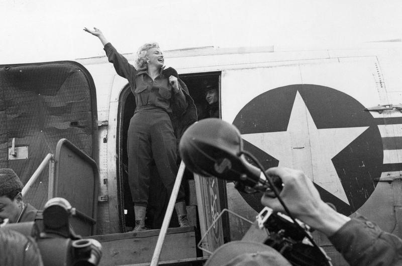 Whoops of joy filled the air as Marilyn Monroe waves an exuberant hello (upper left) as she prepares to debark from the plane that carried her to Seoul.